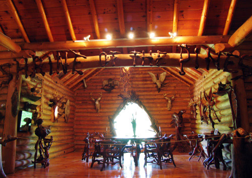"Naturally formed letters spell out ""Shrine of the Pines"" across a beam in the great room"