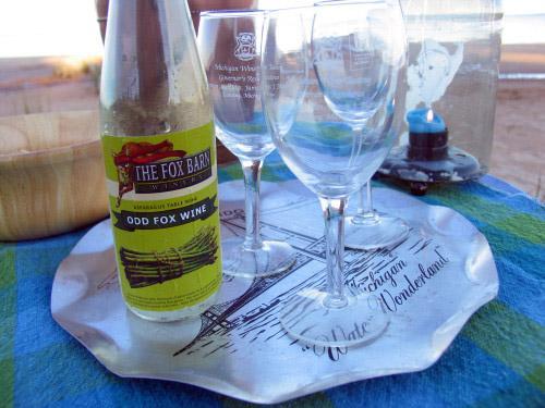 A bottle of Odd Fox asparagus wine on a Lake Michigan beach