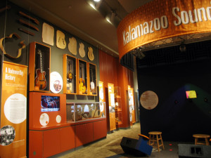 A museum exhibit explains that Orville Gibson founded his mandolin and guitar manufacturing company in Kalamazoo in 1902