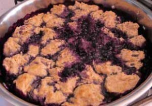 Dabs of dough top the berry mixture and steam cook under the skillet lid