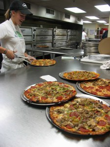 A young lady uses scissors to cut the ultra-thin pizzas, fresh from the 10 Baker's Pride pizza ovens behind her