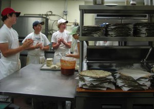 A team of teens preps the dough that fills the stacks of pizza pans in the foreground